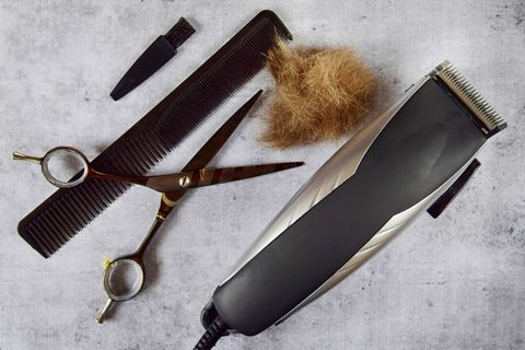 hairdressing art scissors, comb and hair clipper with cut hair on a concrete gray background close up