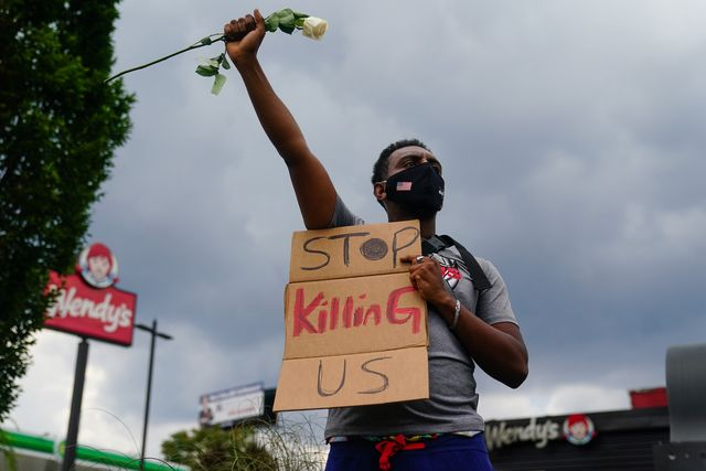 topshot   a man holds a sign and a white rose in his fist while facing traffic outside a burned wendys restaurant on the second day following the police shooting death of rayshard brooks in the restaurant parking lot june 14, 2020, in atlanta, georgia   the fatal shooting of a black man by a white police officer, this time in atlanta, georgia, poured more fuel june 14, 2020 on a raging us debate over racism after another round of street protests and the resignation of the city's police chief a wendy's restaurant where 27 year old rayshard brooks was killed was set on fire june 13, 2020 and hundreds of people marched to protest the killing photo by elijah nouvelage  afp photo by elijah nouvelageafp via getty images