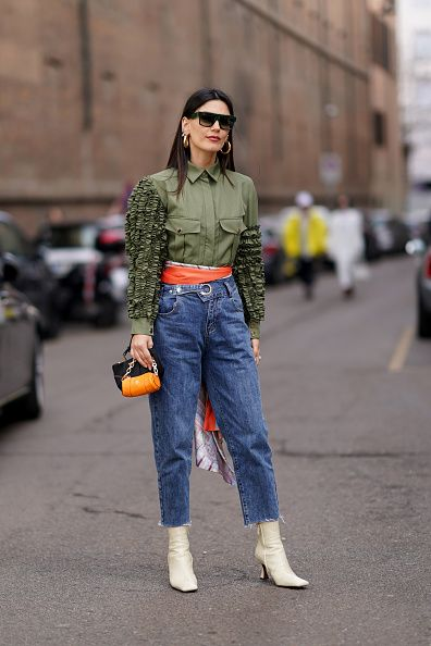 milan, italy   february 21 asena saribatur wears earrings, sunglasses, a green shirt with ruffled sleeves and pockets, an orange scarf around the waist, blue denim cropped jeans, an orange bag, white leather pointy boots, outside sportmax, during milan fashion week fallwinter 2020 2021 on february 21, 2020 in milan, italy photo by edward berthelotgetty images