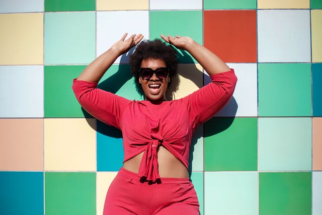 young woman in stylish casuals and sunglasses looking excited against multicolored tiled wall african american female looking at camera and smiling