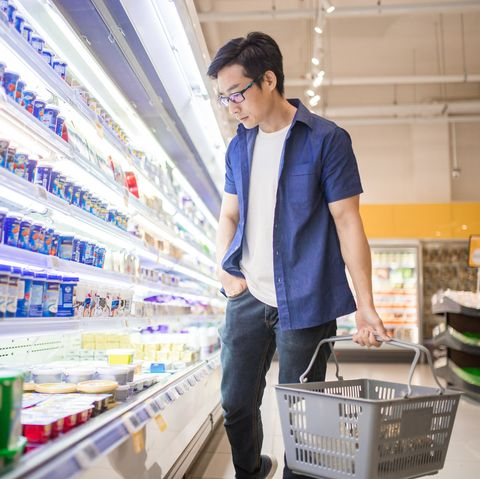 a chinese mature man holding basket and browses for products in the frozen goods section