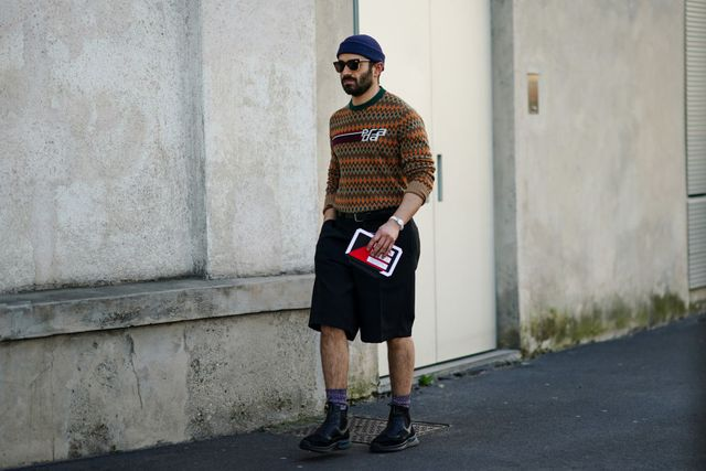 milan, italy   february 20 a guest wears a blue beanie hat, sunglasses, a prada wool pullover, black shorts, socks, black leather shoes, outside prada, during milan fashion week fallwinter 2020 2021 on february 20, 2020 in milan, italy photo by edward berthelotgetty images