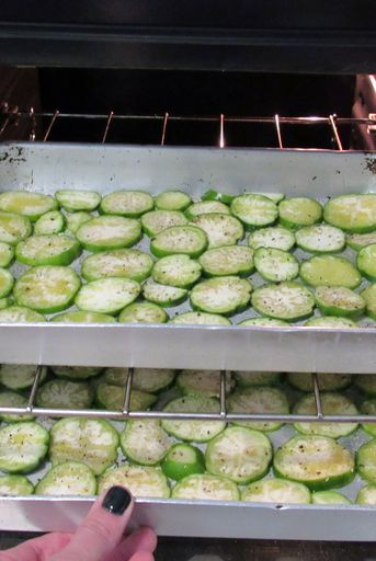 zucchini on a baking sheet being put in the oven to grill