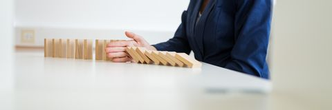 wide view image of unrecognizable business woman sitting at her white office desk stopping collapsing dominos with her hand in a conceptual image of crisis management