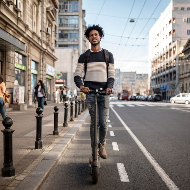 front view of a young african american man exploring the city using a scooter