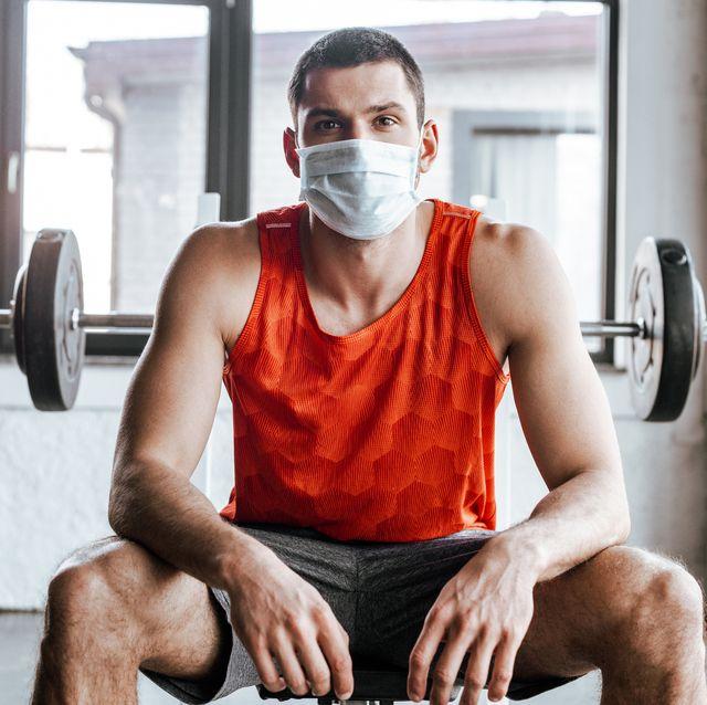 athletic sportsman in medical mask sitting near barbell in gym
