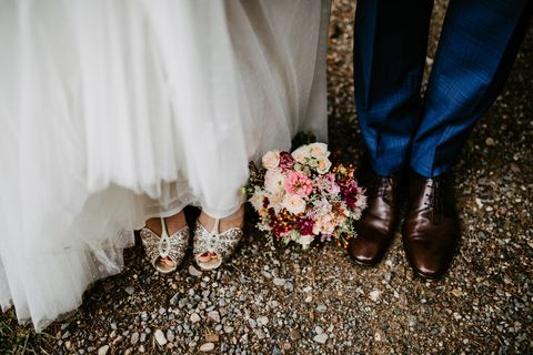 top view of bride and grooms shoes with bridal bouquet