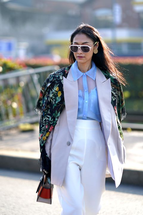milan, italy   february 19 fashion blogger pornwika wears sunglasses, earrings, a gucci floral print scarf over the shoulders, a blue mesh shirt, a gray oversized blazer jacket, white pants, outside gucci, during milan fashion week fallwinter 2020 2021, on february 19, 2020 in milan, italy photo by edward berthelotgetty images