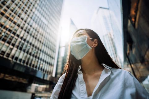 young asian businesswoman with protective face mask to protect and prevent from the spread of viruses during the coronavirus health crisis, standing in an energetic and prosperous downtown city street against corporate skyscrapers
