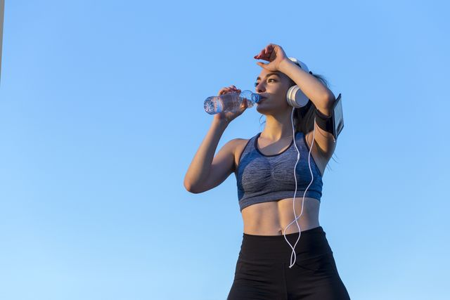 happy girl holding a bottle of water when listening music outdoors