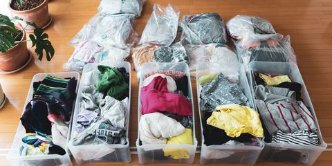 a woman organizes clothes in living room of her home