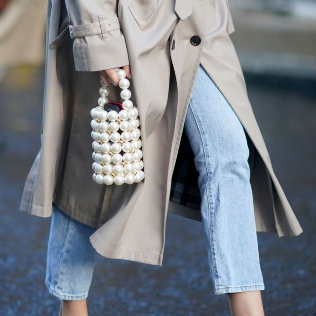 london, england   february 16 a guest wears a trench coat and a beaded pearl bag, blue jeans, during london fashion week fall winter 2020 on february 16, 2020 in london, england photo by edward berthelotgetty images
