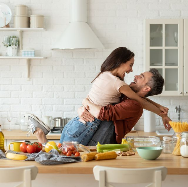 happy husband and wife having fun during cooking at home kitchen excited man hugging and carrying loving woman, cozy bright loft interior with table full of fresh healthy groceries food laughter fun