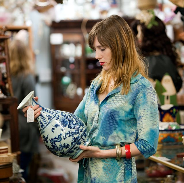 Woman inspecting vase in antiques shop