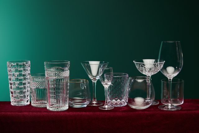 set of glasses old fashioned glass, cocktail glass, champagne glass, highball glass, liqueur glass, brandy glass, cognac balloon and collins glass on green background