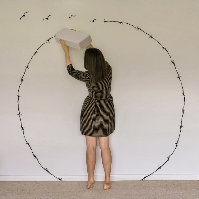 surreal portrait of a woman surrounded by barbed wire, escaping by using a giant eraser