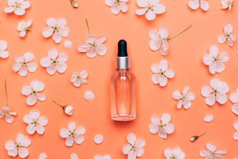 natural cosmetics oil on a coral flower background spring care concept flat lay style