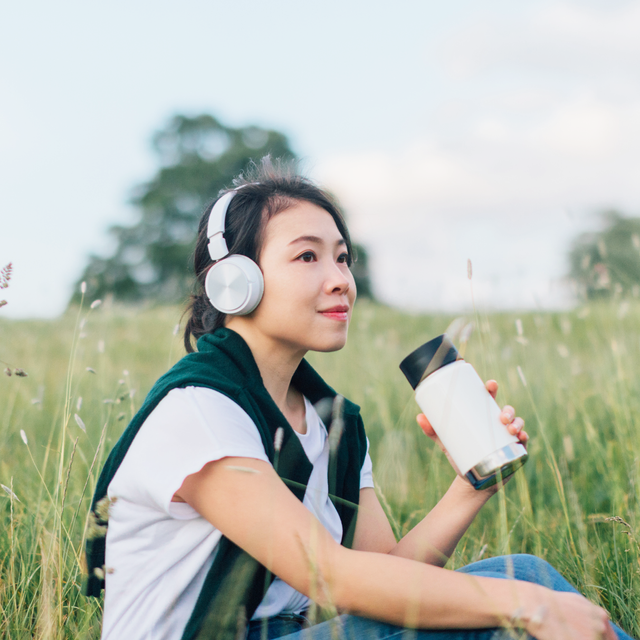 asian woman sitting in green field with headphones and water bottle