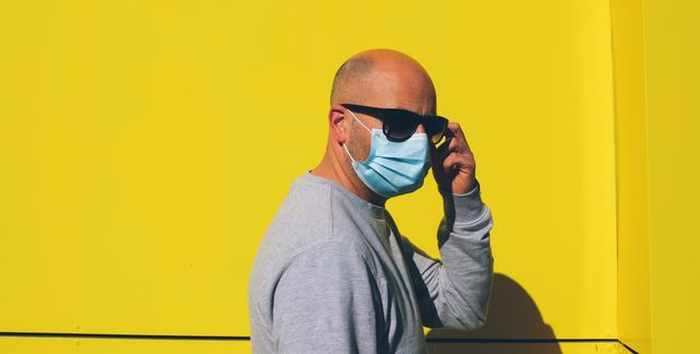 man wearing a face mask against yellow wall