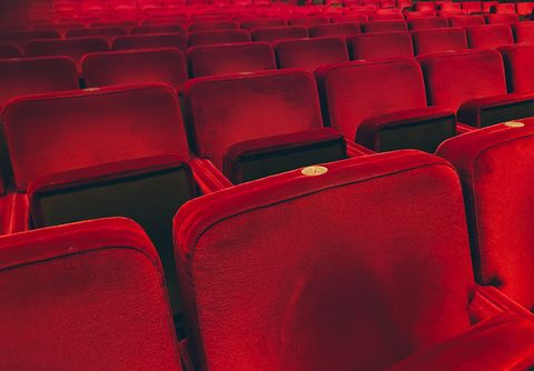 empty red velvet armchairs illuminated inside a concert hall