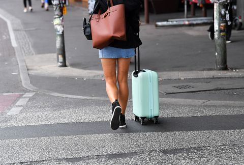 15 july 2020, berlin a woman walks down a street with a wheeled suitcase photo jens kalaenedpa zentralbildzb photo by jens kalaenepicture alliance via getty images