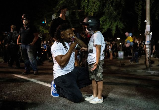 wall of vets organizer leshan terry of portland l and his son leshan terry jr, 6, fix their masks as they stand near members of the wall of vets