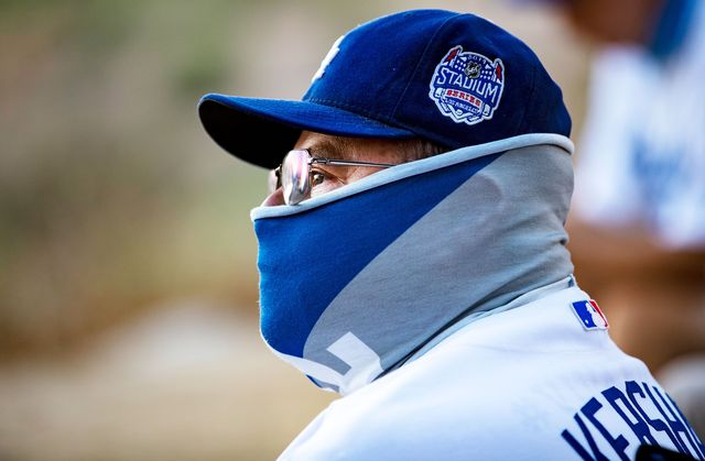 man with baseball cap and neck gaiter