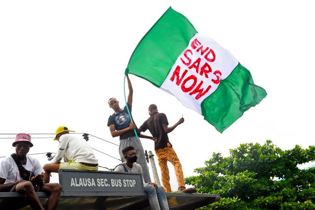 a protester waves the nigerian national flag while gathering with other protesters to barricade the lagos   ibadan expressway, the oldest highway and major link to all parts of the country, during a demonstration to campaign against police brutality and scrapping of the special anti robbery squad sars in lagos, on october 15, 2020   nigerian youth continued to march against police violence in several major cities across the country on october 15, 2020, despite further attacks on processions by men armed with sticks and machetes