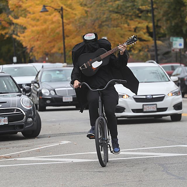 slam dunkle the headless horseman cyclist riding through downtown concord, massachusetts while playing guitar