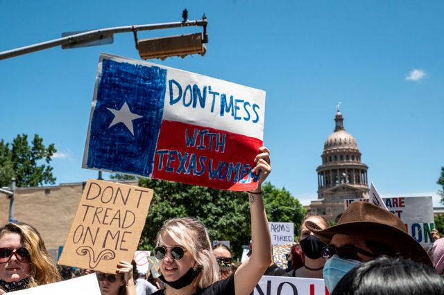 austin, tx   may 29 protesters hold up signs as they march down congress ave at a protest outside the texas state capitol on may 29, 2021 in austin, texas thousands of protesters came out in response to a new bill outlawing abortions after a fetal heartbeat is detected signed on wednesday by texas governor greg abbot photo by sergio floresgetty images