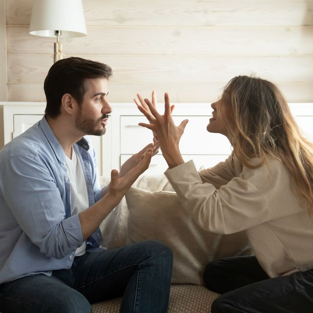 emotional annoyed stressed couple sitting on couch, arguing at home angry irritated nervous woman man shouting at each other, figuring out relations, feeling outraged, relationship problems concept