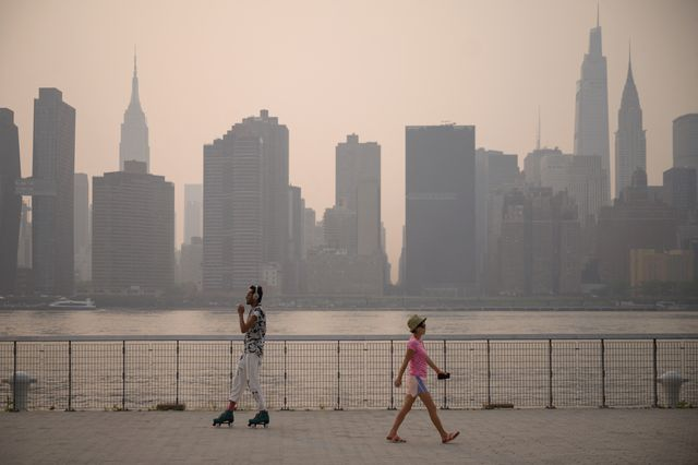 a man skates as a woman walks before the manhattan city skyline at a park in the brooklyn borough of new york on july 20, 2021   domestic media reported that smoke from wilfires buring on the west coast had made its way across the country as world air quality project published an air quality index reading of 172, or unhealthy for new york city photo by ed jones  afp photo by ed jonesafp via getty images