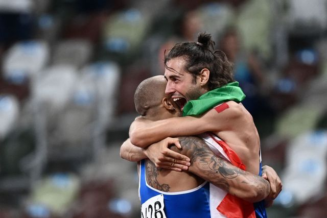 italys lamont marcell jacobs l celebrates with italian athlete gianmarco tamberi after winning the  mens 100m final during the tokyo 2020 olympic games at the olympic stadium in tokyo on august 1, 2021 photo by jewel samad  afp photo by jewel samadafp via getty images