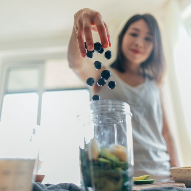 low angle view of a beautiful young asian woman throwing blueberry into the blender to make a healthy smoothie with banana, spinach and vegan milk