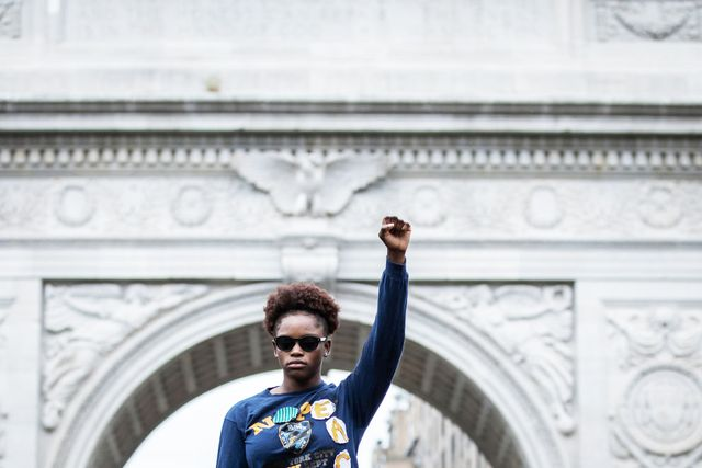 """manhattan, ny   june 02  a protester holds up a raised fist with a shirt that has patches that spell out, """"no peace"""" as she addresses the crowd assembled in washington square park with the washington square arch behind her protesters walked from foley square to washington square park for a peaceful moment of reflection for those that have been killed  protesters took to the streets across america after the killing of george floyd at the hands of a white police officer derek chauvin that was kneeling on his neck during his arrest as he pleaded that he couldn't breathe the protest are attempting to give a voice to the need for human rights for african american's and to stop police brutality against people of color  many people were wearing masks and observing social distancing due to the coronavirus pandemic  leaders of the protest were clear that they wanted it to be a peaceful protest in light of nights of unrest looting and destruction  photographed in washington square park in the manhattan borough of new york on june 02, 2020, usa  photo by ira l blackcorbis via getty images"""