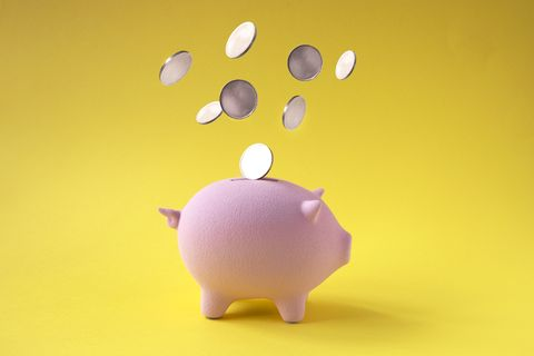 coins falling into pink piggy bank on yellow background