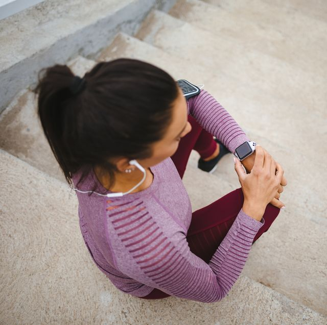 young woman sitting on the stairs and checking her running time on smart watch