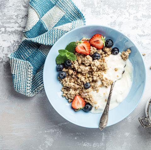 overhead schoot of granola with nuts mix, yogurt, fresh berries and honey on blue plate voor healthy breakfast, top view, copy space