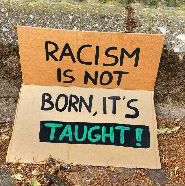 sign that reads racism is not born, it's taught