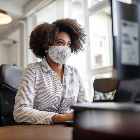 businesswoman with face mask working at her desk looking at computer monitor, in office female professional back to work after covid 19 pandemic lockdown