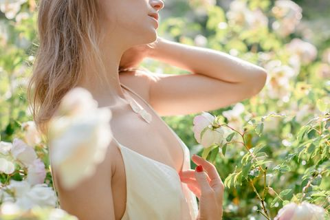 close up of female neck and shoulders beautiful aucasian blonde woman posing among white roses bushes perfume and skincare concept