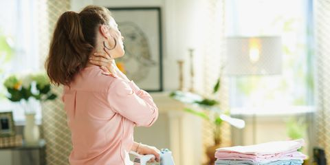 seen from behind woman in pink shirt and white pants with pile of folded ironed clothes having neck pain while ironing on ironing board in the living room in sunny day