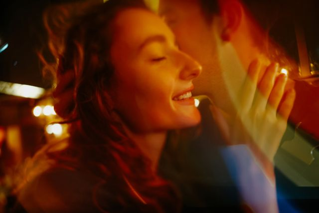 young happy girl in the bright multicolor lights is smiling and looking away she hugs her boyfriend gently only his chin and neck are seen