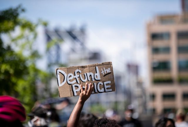 """manhattan, ny   june 19  a protester holds up a homemade sign that says, """"defund the police"""" with the manhattan bridge behind them as they perform a peaceful protest walk across the brooklyn bridge  this was part of the unite ny 2020, bringing all of new york together rally and march for black lives matter as protests that happened around the country to celebrate juneteenth day which marks the end of slavery in the united states protesters continue taking to the streets across america and around the world after the killing of george floyd at the hands of a white police officer derek chauvin that was kneeling on his neck during for eight minutes, was caught on video and went viral  during his arrest as floyd pleaded, """"i can't breathe"""" the protest are attempting to give a voice to the need for human rights for african american's and to stop police brutality against people of color  they are also protesting deep seated racism in america   many people were wearing masks and observing social distancing due to the coronavirus pandemic  photographed in the manhattan borough of new york on june 19, 2020, usa  photo by ira l blackcorbis via getty images"""