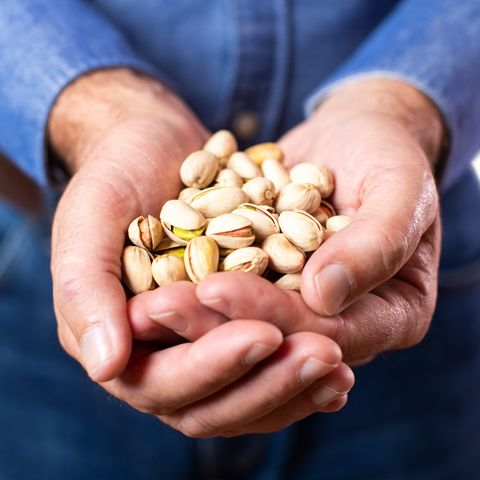 close up studio shot of mature man holding handful of pistachio nuts