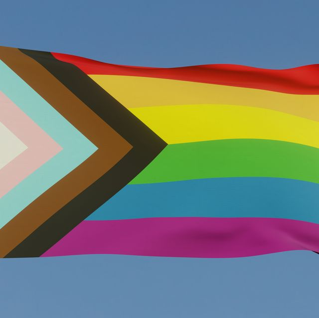 the inclusive lgbtqi pride flag with colours to include people of colour and the trans community on a flag pole in the sun