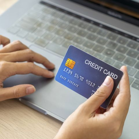 hand holding credit card and using laptop businesswoman or entrepreneur working from home