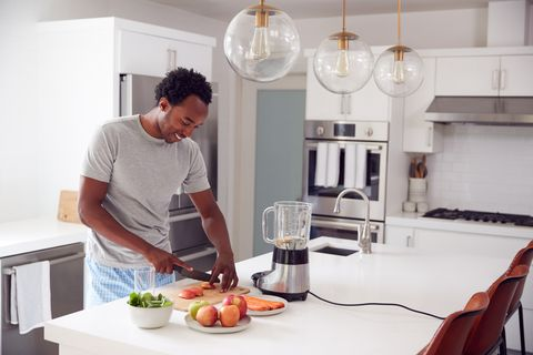 man wearing pyjamas standing in kitchen chopping fruit and vegetables for fresh smoothie
