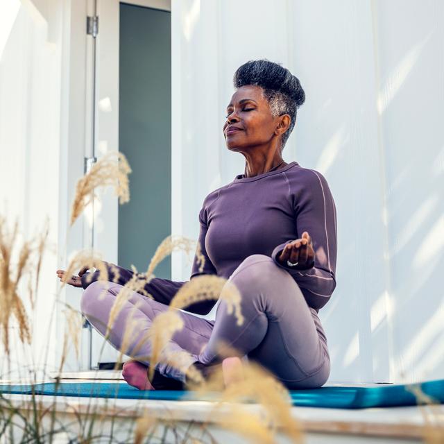 mature black woman practicing yoga on mat outside