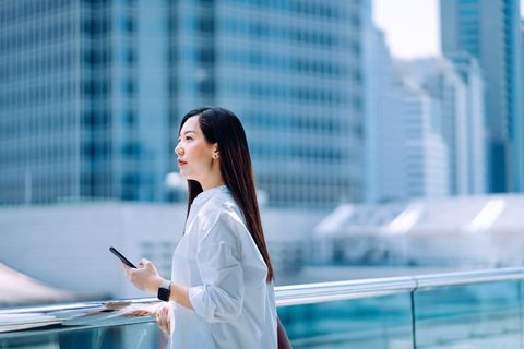 confidence young asian businesswoman holding smartphone standing on the urban balcony of office building looking over the city and planning about the future